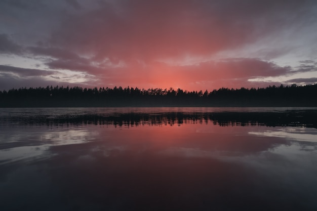 A cloud illuminated by the setting sun over a picturesque forest lake Premium Photo