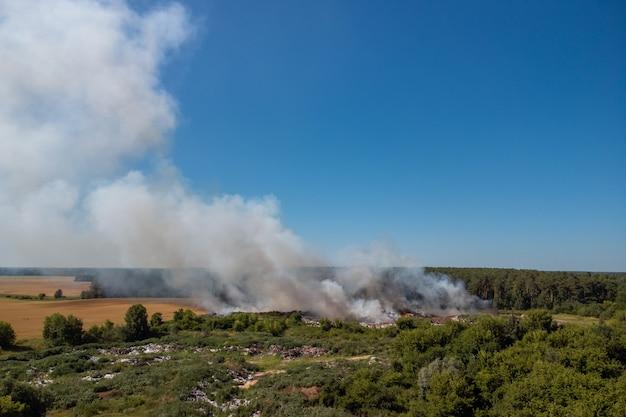공기를 오염시키는 불타는 쓰레기에서 내뿜는 유독 한 연기의 구름