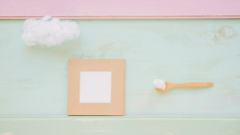 Cloud on wooden spoon and frame on color textured