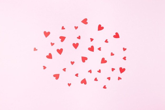 Cloud of red hearts for valentine's day greeting card on pink background