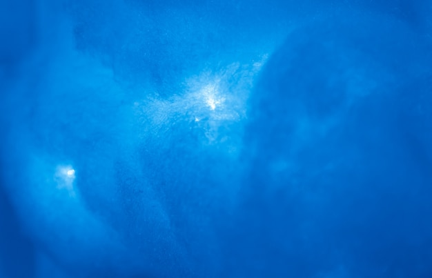 A cloud that is made of medical cotton wool and illuminated in red. the abstract background is the texture of the blue sky.
