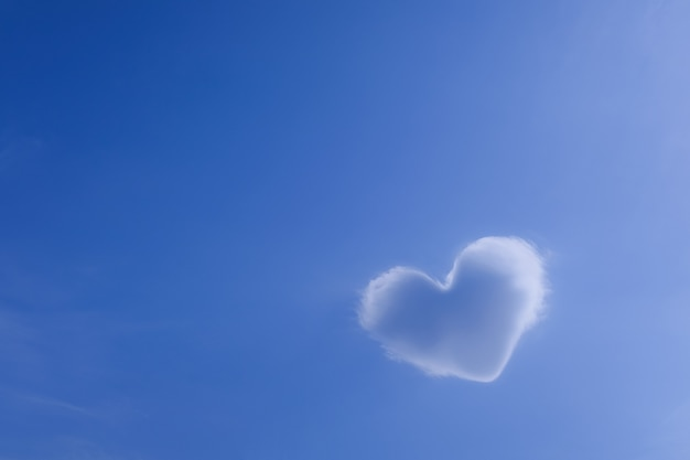 A cloud of white in the shape of a heart against a beautiful idyllic blue sky, a symbol of love. the concept of imagination, valentine's day background