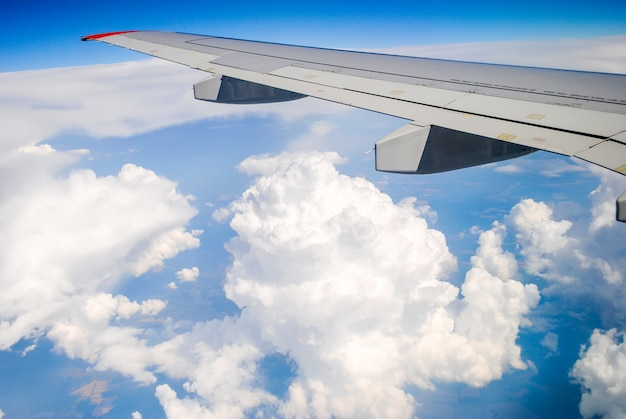 Cloud under the wing on the airplane during flight altitude.