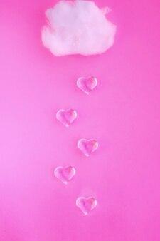 파스텔 핑크 배경에 심장 비와 구름. 창의적인 아이디어. 배너의 최소 개념