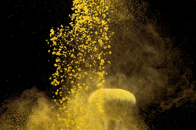 Cloud of yellow makeup powder and brush on dark background