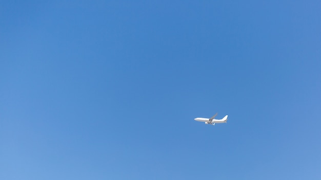 Безоблачное голубое небо, над которым летит самолет.