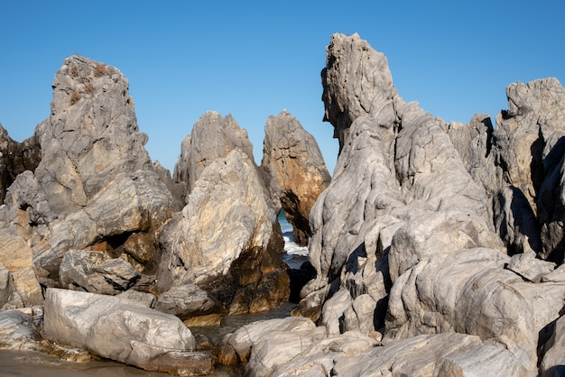 A cloudless blue sky and sea rocks of various shapes.