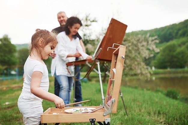 曇りの天気。祖母と祖父は孫娘と屋外で楽しんでいます。絵画の構想