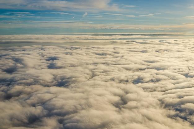 航空機の窓から見た雲と空。