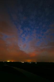 Облака ночью на фоне ярких звезд в небе после захода солнца.