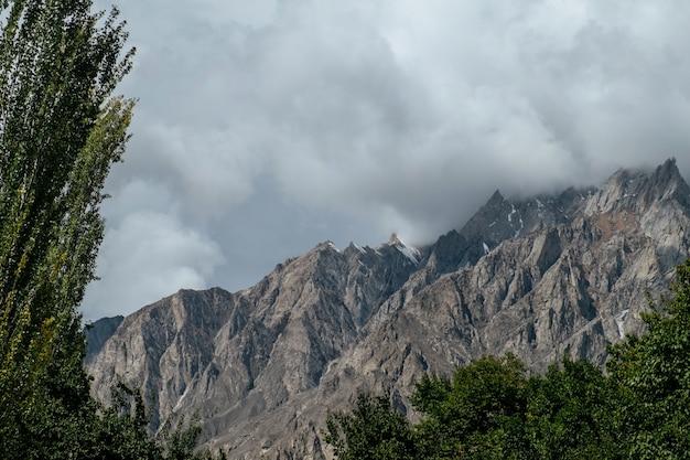 Clouds covered snow capped mountain peaks in karakoram range. gilgit baltistan, pakistan.