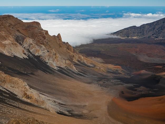 하와이 마우이의 할레아 칼라 국립 공원에있는 계곡을 기어 오르는 구름.