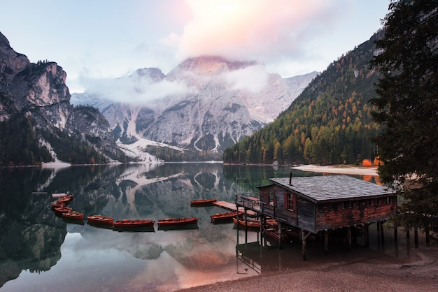 Clouds filled with sunlight. good landscape with mountains. touristic place with wooden building and pear