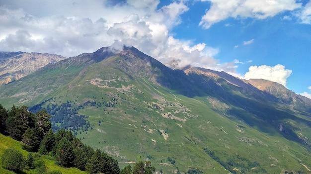 雲が緑の山の上を飛ぶ