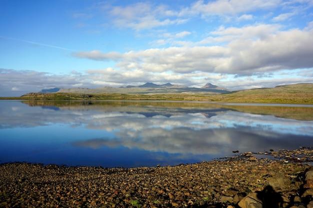 朝の湖の穏やかな水に反射する青い空の雲。