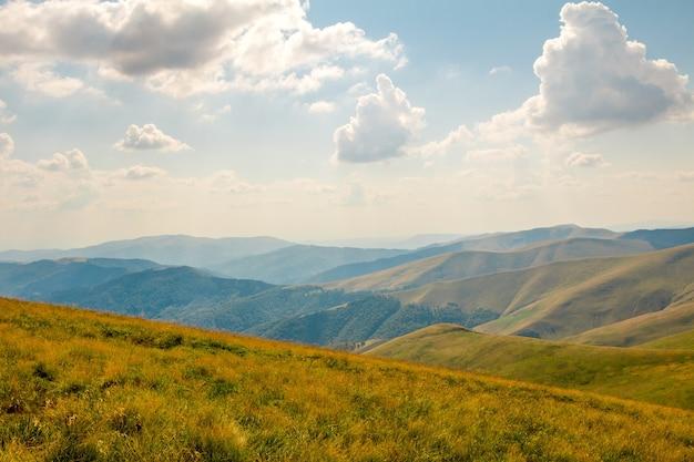 古い山々の頂上にある青い空の雲