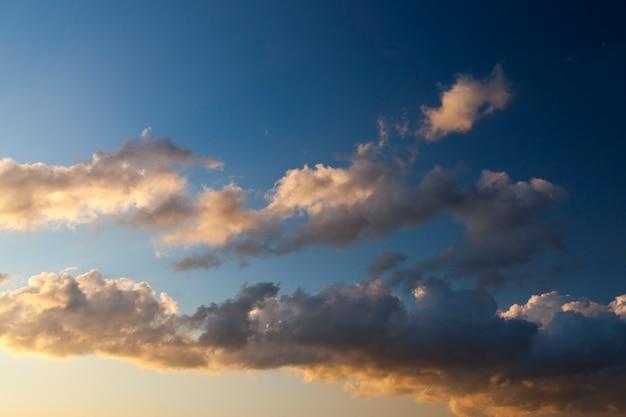 햇빛에 푸른 하늘에 흰색과 회색 색상의 구름.