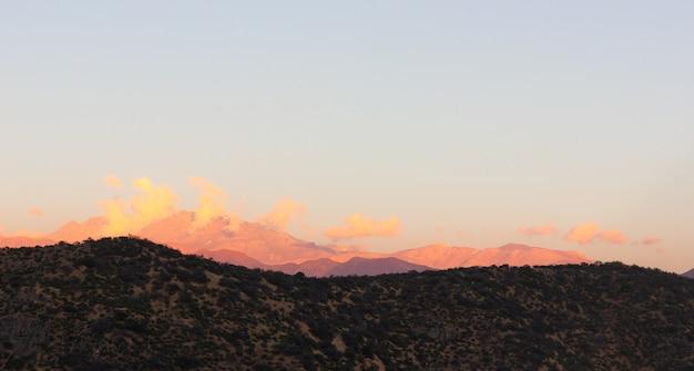 アンデス山脈の頂上の雲は雪で覆われ、サンティアゴの日没時にオレンジ色に点灯しました