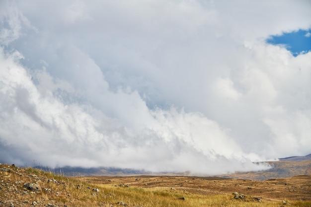 草原の広場の上の雲、丘の上の嵐の雲。アルタイのウコク高原。素晴らしい寒い風景。周りの人