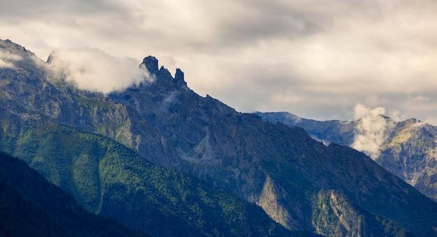 ロッキー山脈の頂上に雲があります。ロシアのコーカサスで撮影。