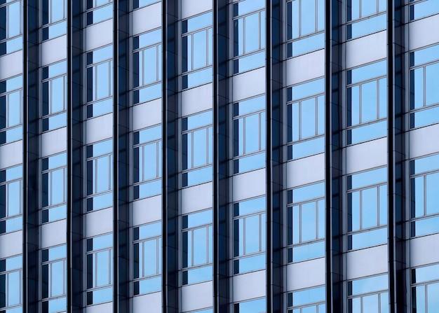 近代的なオフィスビルの窓に映る雲