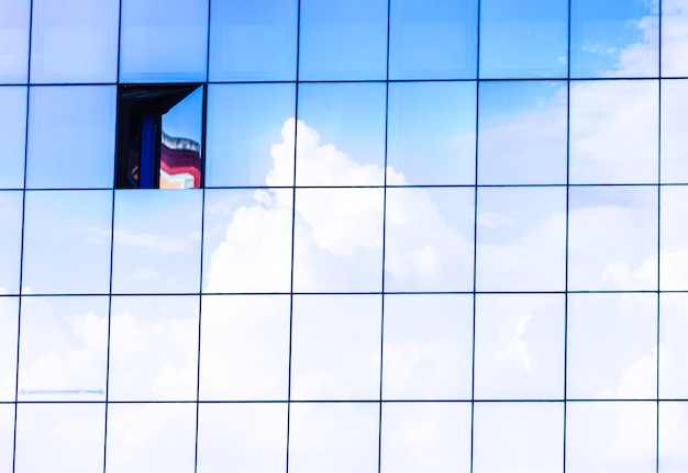 Clouds reflected in windows of modern skyscraper office building. with a windows open.