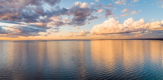 黄金の夕日で穏やかな海に映る雲