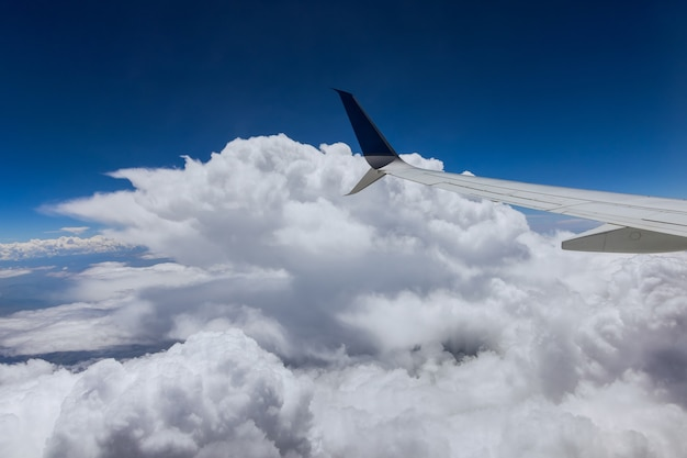 Clouds in the sky as seen on a wing of an airplane flying