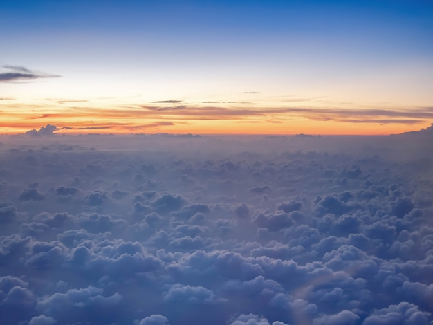Above the clouds twilight sky on high attitude level from airplane, fluffily clouds like heaven