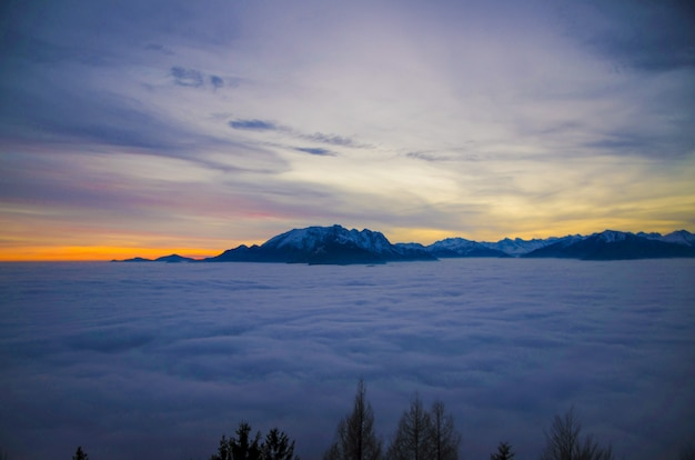 Cloudscape surrounded by rocky mountains covered in the snow during the sunset in switzerland