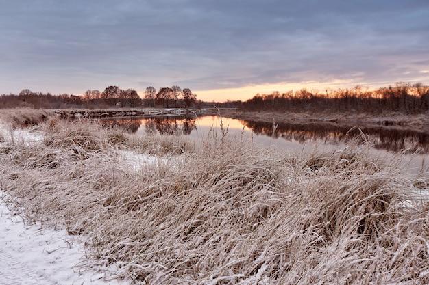 曇りの秋の夜明け。秋の川で最初の雪。
