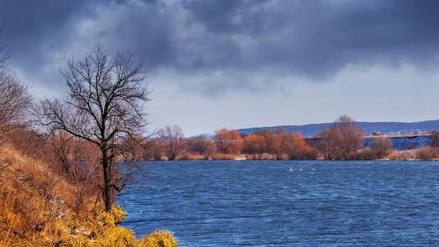 曇りの秋の風景。雨の前の川と暗い嵐の空