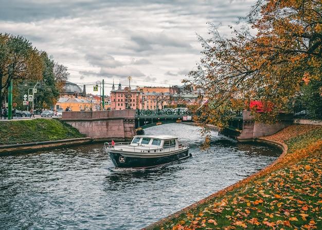 サンクトペテルブルクの曇りの秋の景色、川に船があります。