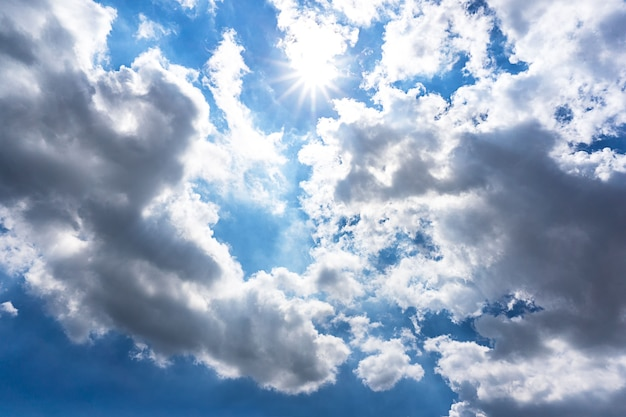 Cloudy blue sky and sun shining background