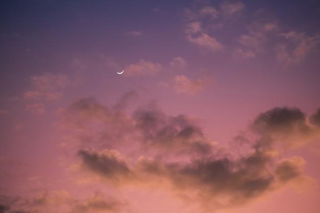 흐린 분홍색과 보라색 하늘입니다. 달과 별 일몰