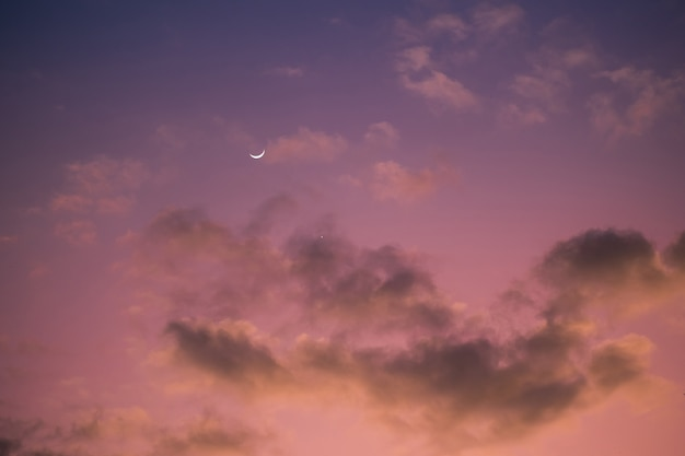 Cloudy pink and purple sky. moon and star in sunset