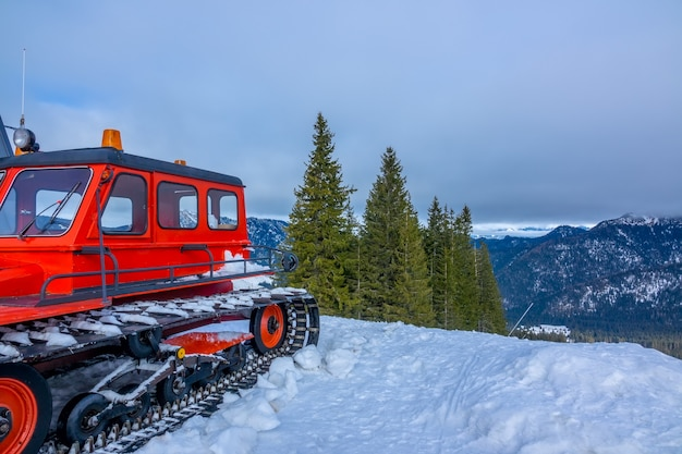 Cloudy sky over snow-capped mountain peaks. wooded slopes. red snowcat in the foreground