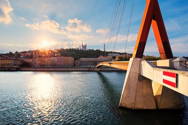 リヨンのソーヌ川の川岸から見たヴューリヨンとフルヴィエール大聖堂に沈む曇りの夕日。