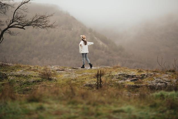 흐린 날씨, 차분한 분위기. 손으로 행복한 소녀는 산을 여행합니다.