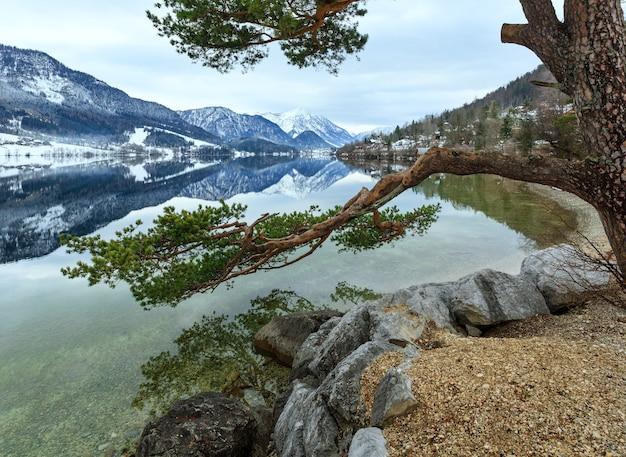 Пасмурная зима. вид на высокогорное озеро grundlsee (австрия) с фантастическим узором-отражением на поверхности воды и сосной на берегу.