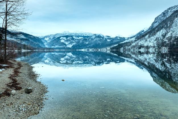 Пасмурная зима. вид на высокогорное озеро grundlsee (австрия) с фантастическим узором-отражением на поверхности воды.