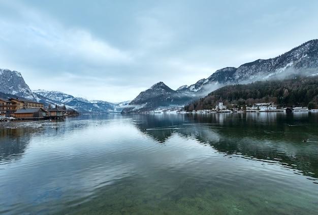 Облачно зимой альпийское озеро grundlsee, вид на австрию