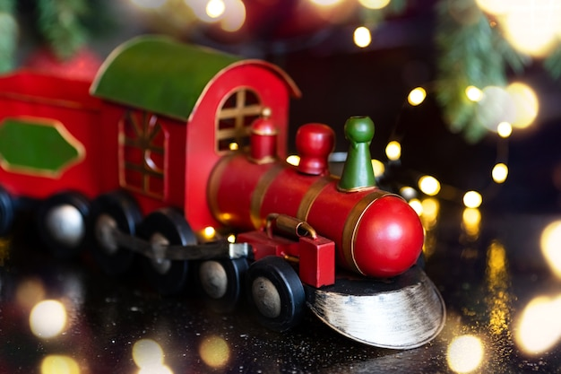 Clouse up christmas toy train near christmas tree