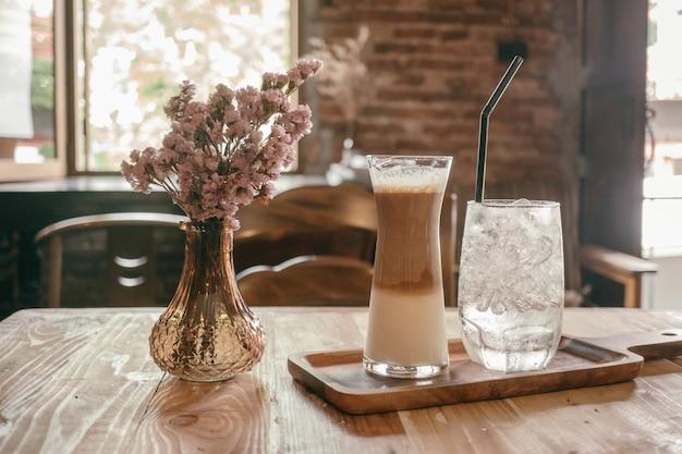 コーヒーショップの背景で新鮮な氷のコーヒー(冷たいカフェラテ)を閉めなさい。