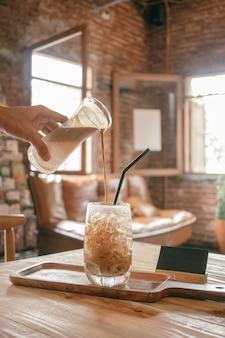 コーヒーショップの背景で新鮮な氷のコーヒー(冷たいラテ)をクローズアップ。