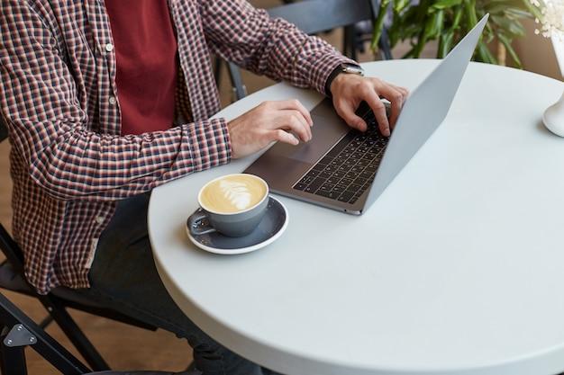 白いテーブルの上のカフェに閉じこもり、灰色のコーヒーの横にあるラップトップのキーボードで男性の手が働いています。