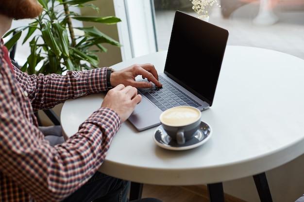 男性の手のクロースアップは、白いテーブル、ほぼ灰色のコーヒーの上のラップトップのキーボードで働いています。