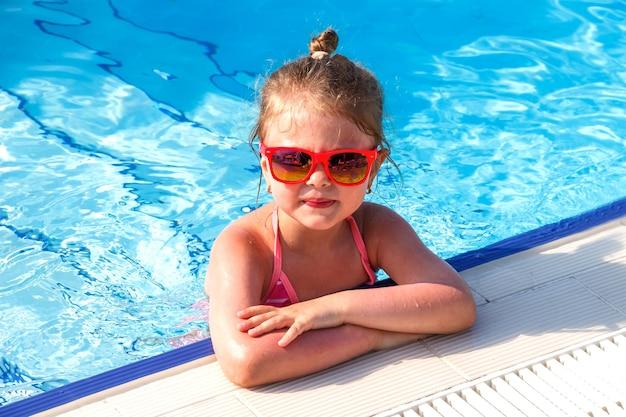 夏のプールで眼鏡をかけた幸せな少女のポートレートをクローズアップ
