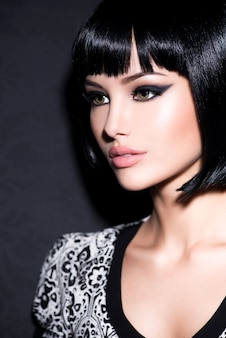 Clouseup portrait of beautiful woman with bright glamour makeup and short black straight hair posing