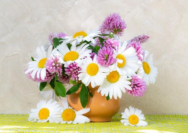 Букет клевера и ромашки в вазе на светлом фоне. летний букет из садовых и полевых цветов. натюрморт с ромашками. выборочный фокус